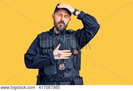 Young handsome man wearing police uniform touching forehead for illness and fever, flu and cold, virus sick
