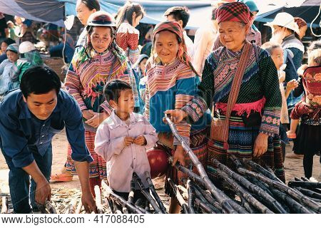 Bac Ha, Vietnam - April 4, 2016: Flower Hmong Tribe In Colorful Traditional Clothing With Their Chil