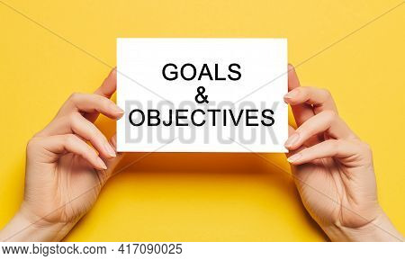 Female Hands Hold Card Paper With Text Goals And Objectives On A Yellow Background. Business And Fin
