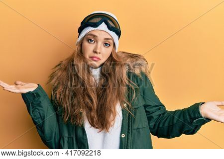 Beautiful blonde caucasian woman wearing snow wear and sky glasses clueless and confused expression with arms and hands raised. doubt concept.