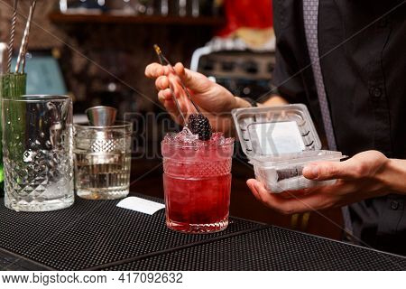 A Male Bartender Uses Tweezers To Carefully Decorate The Finished Cocktail.