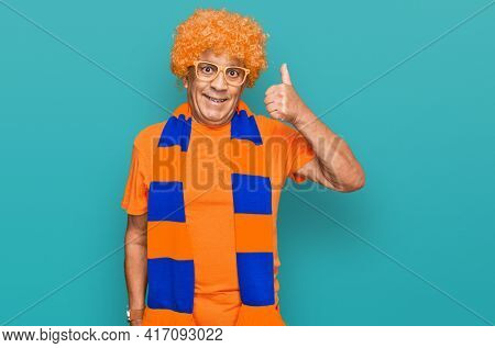 Senior hispanic man football hooligan cheering game smiling happy and positive, thumb up doing excellent and approval sign