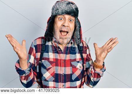 Handsome mature man wearing winter hat with ear flaps celebrating victory with happy smile and winner expression with raised hands