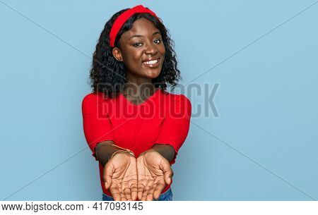 Beautiful african young woman wearing casual clothes smiling with hands palms together receiving or giving gesture. hold and protection