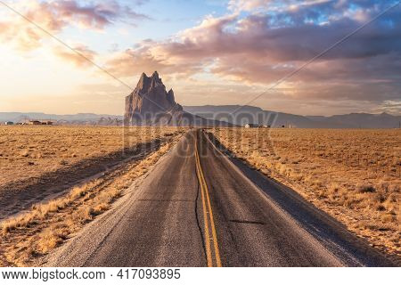 View Of A Road In A Dry Desert With A Shiprock Mountain Peak In The Background. Sunrise Sky Art Rend