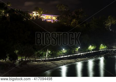 Airlie Beach, Queensland, Australia - April 2021: A Home On A Tree Filled Hillside Lit Up At Night A