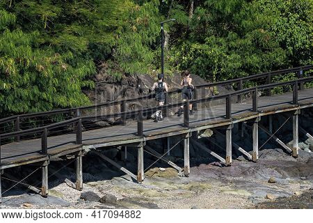 Airlie Beach, Queensland, Australia - April 2021: A Young Couple Jogging Along A Coastal Timber Walk