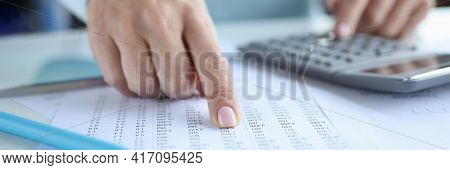 Woman Pointing Finger At Document With Numbers And Counting On Calculator Close-up