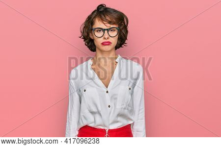 Young hispanic woman wearing business style and glasses depressed and worry for distress, crying angry and afraid. sad expression.