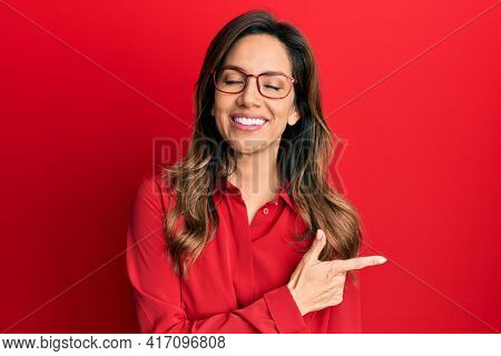 Young latin woman wearing casual clothes and glasses cheerful with a smile of face pointing with hand and finger up to the side with happy and natural expression on face