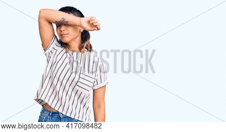 Young woman wearing casual clothes covering eyes with arm, looking serious and sad. sightless, hiding and rejection concept