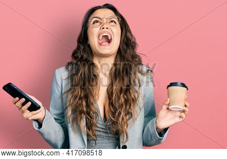 Young hispanic girl using smartphone and drinking a cup of coffee angry and mad screaming frustrated and furious, shouting with anger looking up.