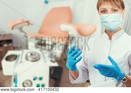 Female gynecologist in protective mask and whitecoat with gynecological vaginal retractor in hand