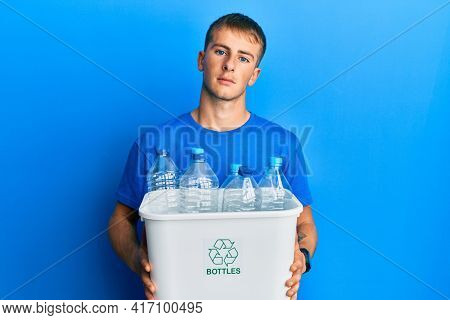 Young caucasian man holding recycling wastebasket with plastic bottles relaxed with serious expression on face. simple and natural looking at the camera.