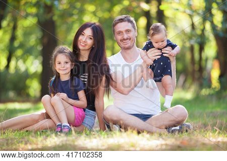 Happy mother, father, son and daughter in the park. Beauty nature scene with family outdoor lifestyle. Happy family resting together sitting on the grass, having fun outdoor. Happiness and harmony