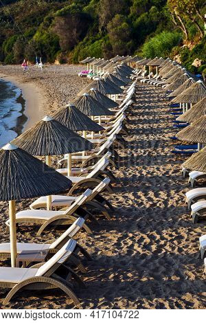 Umbrellas And Sun Beds On The Sandy Beach Of Zakynthos In Greece
