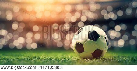 Football soccer ball on grass field on stadium, evening match. 3D render