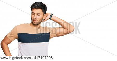 Young handsome man wearing casual clothes suffering of neck ache injury, touching neck with hand, muscular pain