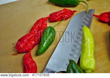 Fresh Jalapeno Habanero Banana Pepper And Knife On A Wooden Cutting Board