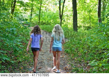 Two Little Girls Taking A Hike Through The Woods