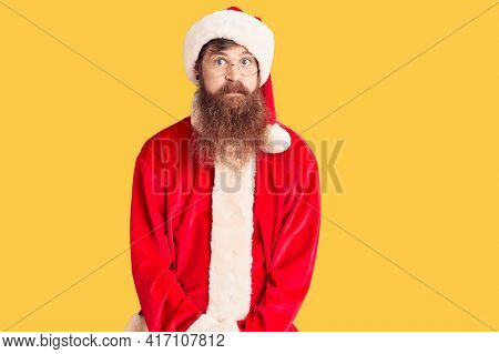 Handsome young red head man with long beard wearing santa claus costume puffing cheeks with funny face. mouth inflated with air, crazy expression.