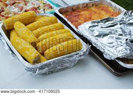 Large Assortment Of Dishes On The Food Table At A Picnic