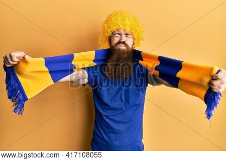 Redhead man with long beard football hooligan cheering game wearing funny wig puffing cheeks with funny face. mouth inflated with air, catching air.
