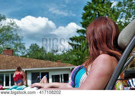 Unrecognizable Young Teen Girl In Bikini Sunbathing Poolside