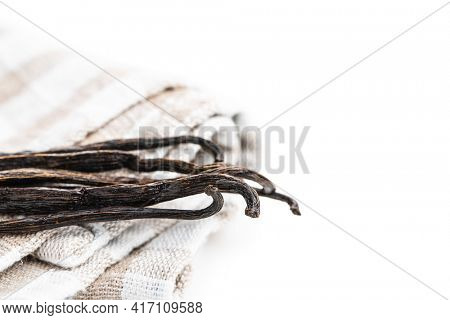 Vanilla pods on checkered napkin. Sticks of vanilla isolated on white background.