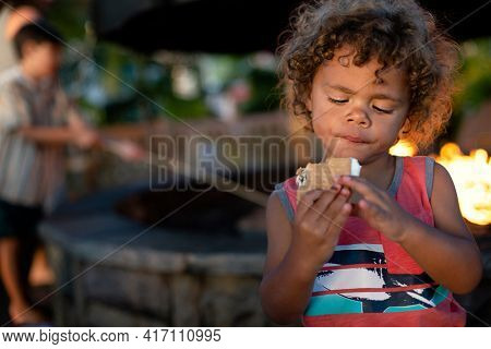 Cute little boy about to eat a smore while sitting by an outdoor fire. Young black boy enjoying s`mores by the campfire at night in the summer time.