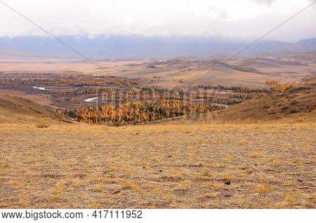 A View Of A Picturesque Autumnal Hilly Valley With A Winding River Flowing Through The Steppe, Surro