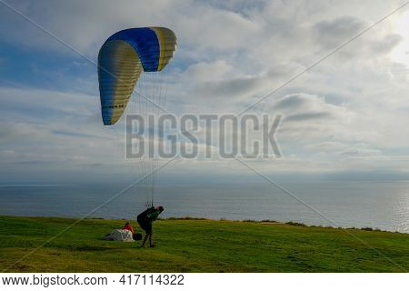 Man Doing Sport, Para-glider In The Clouded Sky. Paragliding Is An Extreme Sport And Recreation. Tor