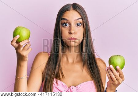 Young hispanic woman holding green apples puffing cheeks with funny face. mouth inflated with air, catching air.
