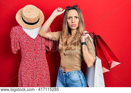 Beautiful hispanic woman holding shopping bags by retail manikin skeptic and nervous, frowning upset because of problem. negative person.
