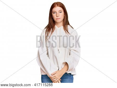 Young read head woman wearing casual sweatshirt with serious expression on face. simple and natural looking at the camera.