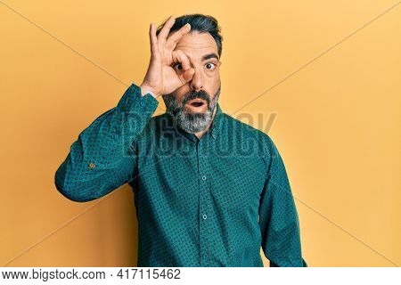 Middle age man with beard and grey hair wearing business clothes doing ok gesture shocked with surprised face, eye looking through fingers. unbelieving expression.