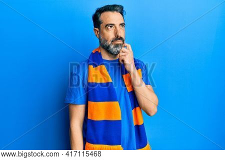 Middle age man with beard and grey hair football hooligan cheering game thinking concentrated about doubt with finger on chin and looking up wondering