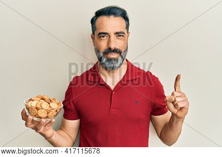 Middle age man with beard and grey hair holding bowl with salty crackers biscuits smiling with an idea or question pointing finger with happy face, number one