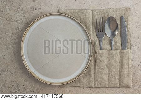 Plate And Cutlery With Linen Napkin On Beige Stone Backgroud. Rustic Table Setting In Natural Warm C