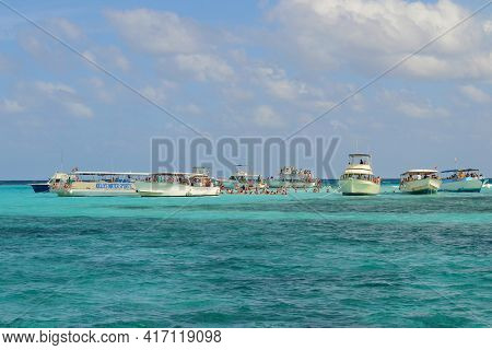 GRAND CAYMAN, CAYMAN ISLANDS - DEC 23, 2012: Tour Boats and private vessles anchored in shallow waters off the island where visitors interact with Manta Rays in the wild.