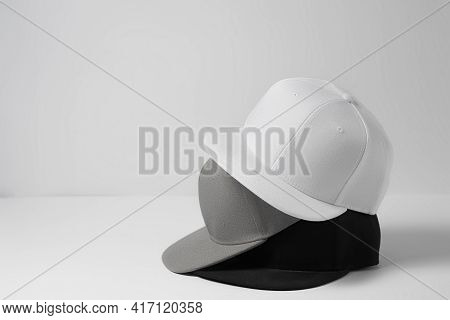 Three Baseball Snapback Hats In Monochrome Black, White And Gray Colors Stacked On Top Of Each Other