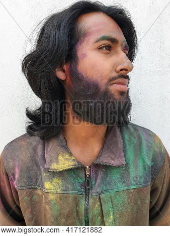 Close Up Portrait Of Young Man Covered With Multicolor Holi Color Powder And Standing Against White