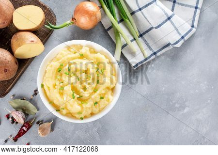Mashed Potatoes With Butter And Fresh Parsley In A White Bowl On Gray Stone Concrete Background. Top