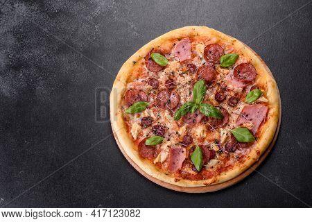 Delicious Fresh Oven Pizza With Tomatoes, Salami And Bacon On A Dark Concrete Background