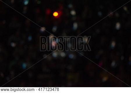 Black Background With Multicolored Blurred Bokeh Spots And A Bright Yellow Spot.