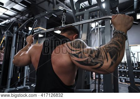 Rear View Low Angle Shot Of A Tattooed Bodybuilder Working Out On Lat Pulldown Gym Machine