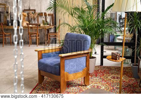 The Interior Is Retro Styled. Wooden Chair With Blue Cladding In The Room.