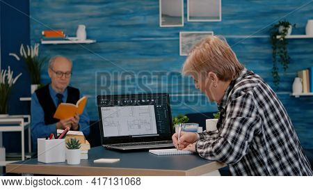 Senior Woman Architect Analysing Digital Prototype With Plans From Laptop