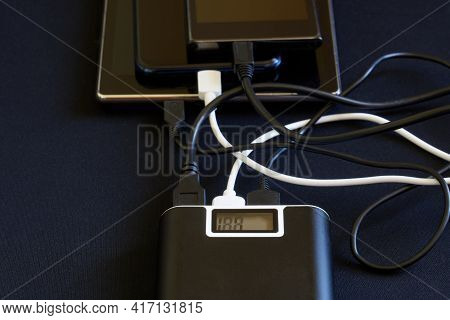 One External Battery - The Powerbank Recharges Three Usb Gadgets: Two Smartphones And A Tablet. Dark