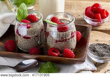 Appetizing, Healthy And Refreshing Chia Seed Pudding With Fresh Raspberries, Mint Leaves And Cookies
